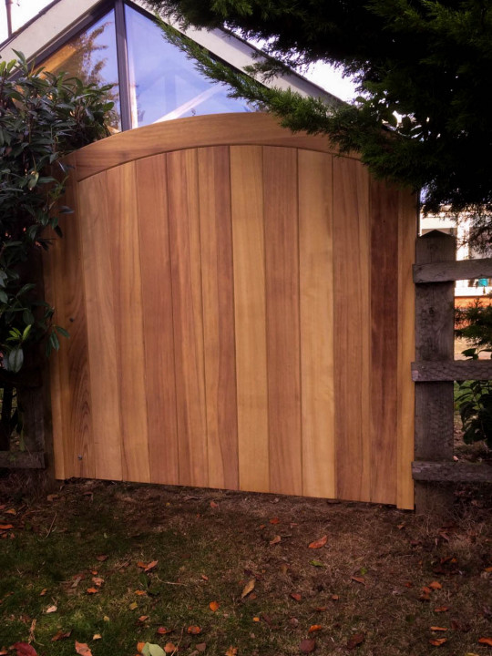 Curved Top Exterior Iroko Gate with no treatment, left to weather silvery-grey