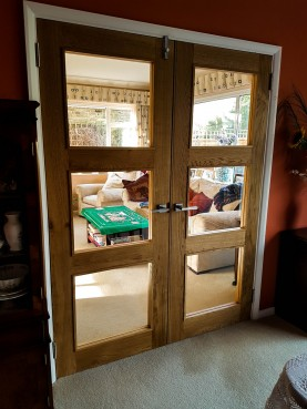 Room dividing glazed oak doors with square glass panes and brushed silver handles
