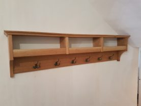 Wall mounted bespoke oak coat rack with hat and glove storage with antique metal coat hooks bespoke joinery hertfordshire