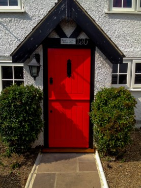 Bright red bespoke stable door in cottage style with antique black door furniture. Joinery herts