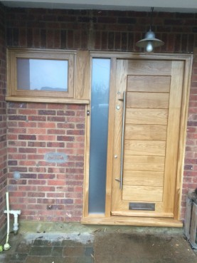 Solid contemporary oak door with frosted glazed side panel and long entrance handle. Bespoke joinery